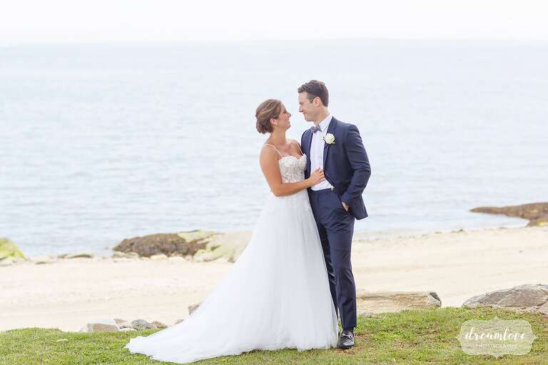 Bride and groom stand on shore at their Connecticut Beach Club wedding in Stamford.