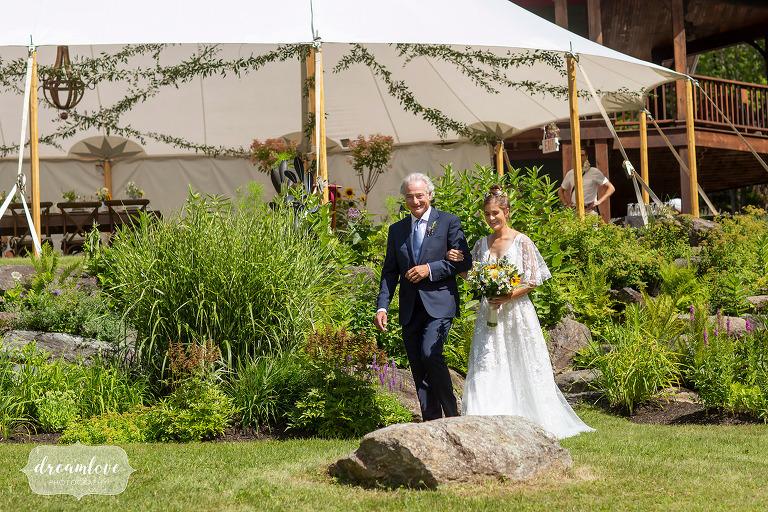Bride enters outdoor wedding reception at Stowe Meadows.