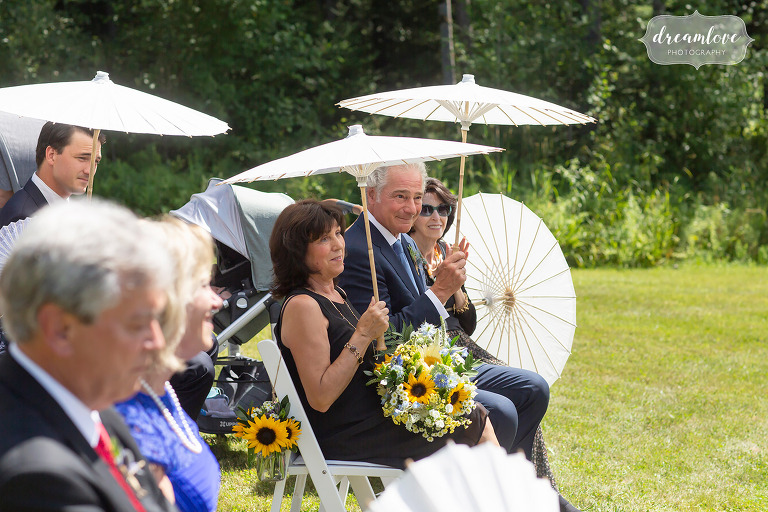 Guests hold parasols up during sunny wedding ceremony.