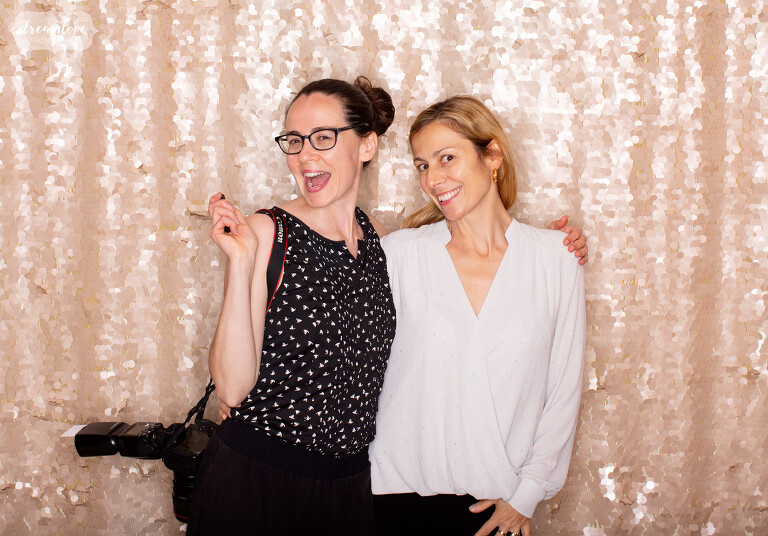Katie Barnes and Ana of North Shore Events pose in a wedding photo booth at Myopia.