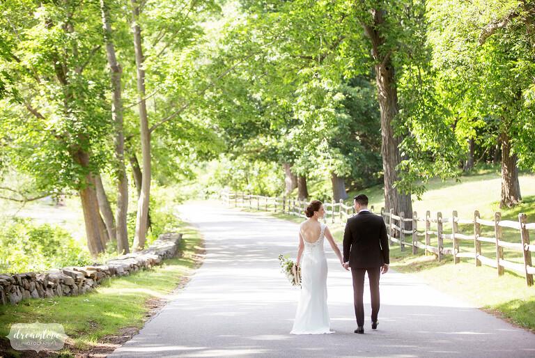 Bride and groom walk down path at Myopia Hunt Club.
